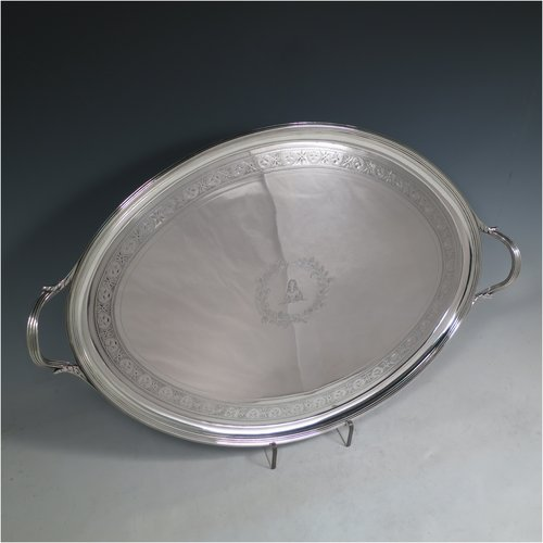 An Antique Georgian Sterling silver oval two-handled tea tray, with a beautifully hand-engraved band of floral decoration, an applied reeded border with matching cast handles, and sitting on a flat base. This handsome Georgian sterling silver tray was made by Elizabeth Jones of London in 1794. The dimensions of this fine hand-made silver tray are length inc. handles 52 cms (20.5 inches), width 34 cms (13.5 inches), and it weighs approx. 1,593g (51 troy ounces).
