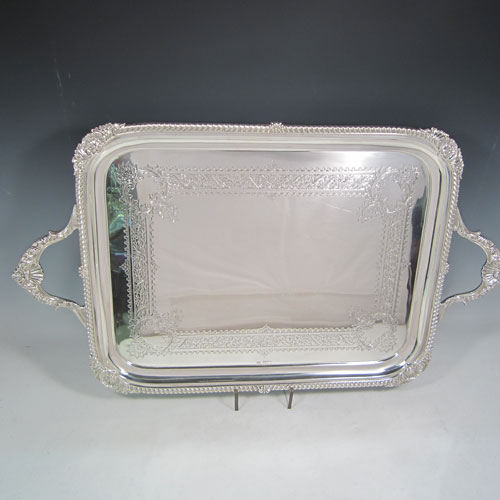 Antique Edwardian sterling silver tea tray, having a rectangular body, with applied cast gadroon and shell border, two cast handles, and a hand-engraved ground with floral decoration, all sitting on a flat base. Made by Mappin and Webb of Sheffield in 1905. The dimensions of this fine hand-made silver tea tray are length (inc. handles) 70 cms (27.5 inches), width 41 cms (16 inches), and it weighs approx. 3,410g (110 troy ounces).