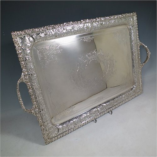 A very pretty Antique Victorian Silver Plated tray, having a rectangular body, a beautiful hand-engraved ground with floral decoration surrounding a central vacant cartouche, a hand-chased border with floral and scroll decoration, with two cast gadroon side-handles, and sitting on a flat base. This beautiful silver-plated tray was made by the Mappin Brothers of Sheffield in their top-quality Queens Plate. The dimensions of this fine hand-made silver plated tea tray are length (inc. handles) 58 cms (22.75 inches), width 38 cms (15 inches).