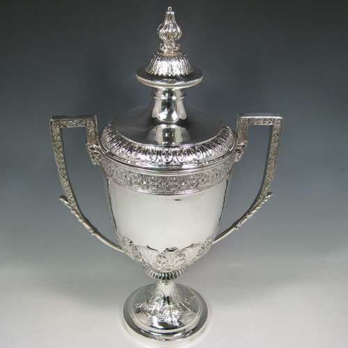 Antique Edwardian large sterling silver trophy cup and cover, having a round hand-chased body with floral and anthemion leaf decoration, two cast handles with rams head masks, original cover with cast floral finial, and sitting on a pedestal foot. Made by Mappin and Webb of London in 1903. Height 49 cms (19.25 inches), spread across arms 31 cms (12.25 inches). Weight approx. 2,300g (74.2 troy ounces).