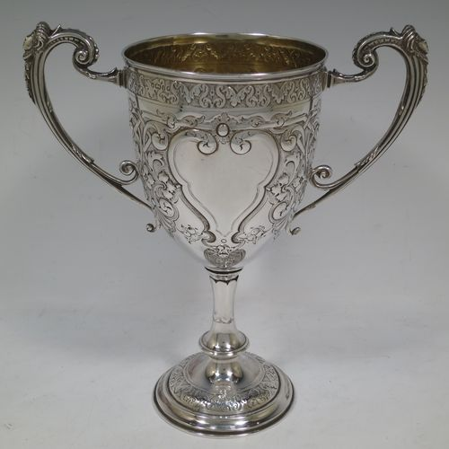A very beautiful Antique Victorian Sterling Silver trophy cup, having a round body with tapering sides all hand-chased with floral and scroll decoration surrounding vacant cartouches either side, two cast scroll handles with figural thumb-pieces, a gold-gilt interior, and all sitting on a pedestal foot. Made by John Edward Bingham and Charles Henry Bingham of Sheffield in 1876. The dimensions of this fine hand-made antique silver trophy cup are height 24 cms (9.5 inches), spread across arms 22 cms (8.75 inches), and it weighs approx. 620g (20 troy ounces).