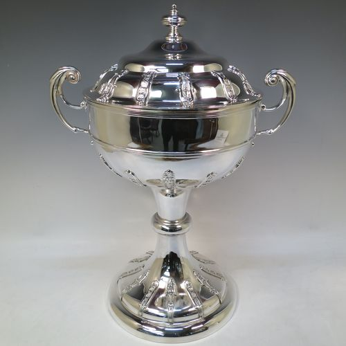 A very impressive and large Antique Edwardian  Sterling Silver trophy cup and cover, having a round body with applied floral strap-work decoration, two flying scroll side-handles, a central applied girdle band, a pull-off lid with matching applied strap-work and a cast round finial, and all sitting on a stepped pedestal foot, again, with matching decoration. Made by Alexander Clark of Sheffield in 1906. The dimensions of this fine hand-made antique silver trophy cup and cover are height 48 cms (19 inches), spread across arms 37 cms (14.5 inches), and it weighs approx. 2,842g (92 troy ounces). Please note that this item has a full armorial crest engraved on one side.