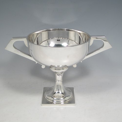 Sterling silver trophy cup, in an Art Deco style having two angular handles, a plain round body, and sitting on a pedestal foot with a square base. Made by the Wilmot Manufacturing Co., of Birmingham in 1927. The dimensions of this fine silver trophy cup are height 15 cms (6 inches), spread across handles 23.5 cms (9.25 inches), and it weighs approx. 361g (11 troy ounces).