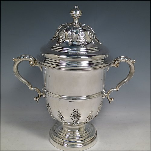 A Sterling Silver trophy cup and cover, in a George II style, having a round body with applied floral strap-work decoration, two scroll side-handles with anthemion leaf thumb-pieces, a central applied girdle band, a pull-off lid with matching applied strap-work and a cast round finial, and all sitting on a stepped pedestal foot. Made by George Bryan & Co., of Birmingham in 1936. The dimensions of this fine hand-made silver trophy cup and cover are height 30 cms (11.75 inches), spread across arms 26.5 cms (10.5 inches), and it weighs approx. 1,132g (36.5 troy ounces).
