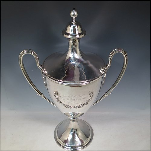 A rare Antique Georgian Sterling Silver large trophy cup and cover, having a neoclassical round plain tapering body with applied laurel-leaf cartouches, with applied reeded borders, two loop side-handles with anthemion leaf shoulders, an original cover with cast finial, and sitting on a round pedestal foot. Made by John Langland II of Newcastle in 1798. The dimensions of this fine hand-made antique silver trophy cup and cover are height 51 cms (20 inches), spread across arms 33 cms (13 inches), and it weighs approx. 3,176g (102 troy ounces). Please note that this trophy is engraved with contemporary presentation inscriptions on both sides.