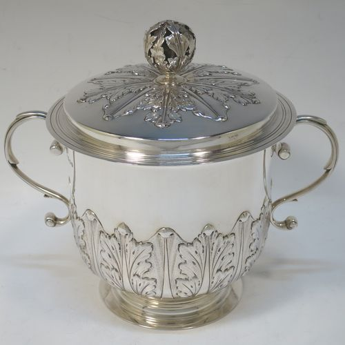 A very handsome Sterling Silver trophy cup and cover, in the shape of a lidded Porringer, having a round body with hand-chased Anthemion leaf decoration, with two scroll side-handles, a lift-off cover with matching decoration and a pierced floral finial, and all sitting on a stepped pedestal foot. Made by Charles Stuart Harris of London in 1925. The dimensions of this fine hand-made antique silver trophy porringer cup are height 18 cms (7 inches), spread across handles 21 cms (8.25 inches), and it weighs approx. 748g (24 troy ounces).