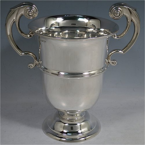 An Antique Edwardian Sterling Silver trophy cup, in a George I style having two flying scroll side-handles, a plain round body with central reeded band, and sitting on a pedestal foot. Made by Walker & Hall of Sheffield in 1910. The dimensions of this fine hand-made antique silver trophy cup are height 21.5 cms (8.5 inches), spread across handles 21 cms (8.25 inches), and it weighs approx. 514g (16.6 troy ounces).