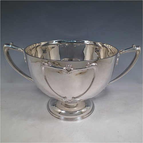An Antique Edwardian Scottish large and heavy Sterling Silver Art Nouveau style trophy bowl, having a round hand-chased body, with two cast scroll and tendril side handles, with two vacant cartouches either side, and all sitting on a pedestal foot. Made by Hamilton & Inches of Edinburgh in 1906. The dimensions of this fine hand-made antique silver trophy bowl are height 23 cms (9 inches), diameter at top of bowl 28 cms (11 inches), and it weighs approx. 2,222g (71.6 troy ounces).