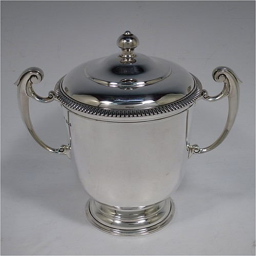 A very handsome Sterling Silver trophy cup and cover, in a George II style, having a plain round body, with two flying scroll side-handles, a pull-off lid with cast finial and applied gadroon border, and all sitting on a stepped pedestal foot. Made by Johnson, Walker, and Tolhurst of London in 1930. The dimensions of this fine hand-made silver trophy cup and cover are height 18 cms (7 inches), spread across arms 20 cms (8 inches), and it weighs approx. 676g (22 troy ounces).
