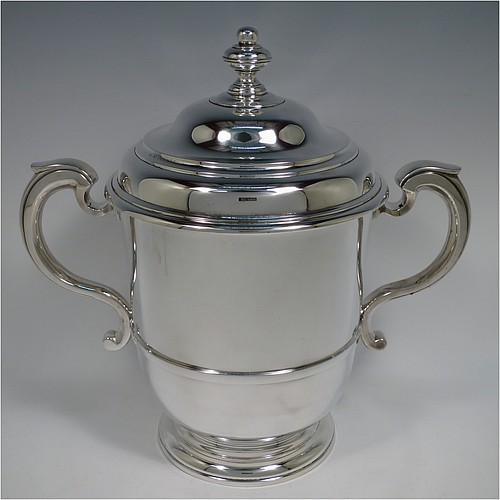 A very heavy Sterling Silver trophy cup and cover in a George II style, having a plain round body with applied reeded borders, two cast scroll side-handles with thumb-pieces, a central applied girdle band, a pull-off lid with matching reeded work and a cast round finial, and all sitting on a stepped pedestal foot. Made by Robert Comyns of London in 1934. The dimensions of this fine hand-made silver trophy cup and cover are height 28 cms (11 inches), spread across arms 30 cms (11.75 inches), and it weighs approx. 1,795g (58 troy ounces).