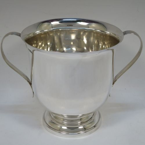 A handsome Sterling Silver trophy cup, having a plain round bellied body, two side-handles with reeded decoration, and sitting on a round stepped pedestal foot. Made by Henry Wilkinson of Sheffield in 1921. The dimensions of this fine hand-made silver trophy cup and are height 15 cms (6 inches), spread across arms 21 cms (8.25 inches), and it weighs approx. 504g (16 troy ounces).
