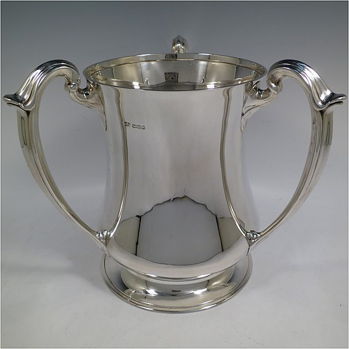 A very handsome and large Sterling Silver Art Nouveau style trophy loving cup, having a plain round bellied body with three scroll handles, and all sitting on a collet foot. Made by Henry Atkins of Sheffield in 1920. The dimensions of this fine hand-made silver trophy loving cup are height 25 cms (9.75 inches), width across handles 27.5 cms (10.75 inches), and it weighs approx. 1,322g (42.6 troy ounces).