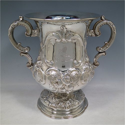 An Antique Victorian Sterling Silver trophy cup, in a Campana style, having a bellied body with cartouches on both sides, with hand-chased floral and scroll decoration, with two floral scroll handles, and sitting on a pedestal foot. Made by Charles Boyton of London in 1861. The dimensions of this fine hand-made antique silver trophy cup are height 26 cms (10.25 inches), spread across handles 30 cms (11.75 inches), and it weighs approx. 1,291g (42 troy ounces). Please note that this item is crested on one side.