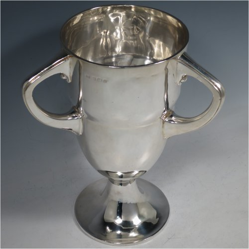 An Antique Edwardian Sterling Silver heavy Arts and Crafts style trophy cup, having a plain round baluster body, with three cast loop side-handles, and sitting on a pedestal foot. Made by David Samuels of Birmingham in 1909. The dimensions of this fine antique silver trophy cup are height 25.5 cms (10 inches), width across handles 20 cms (8 inches), and it weighs approx. 1,016g (32.8 troy ounces).