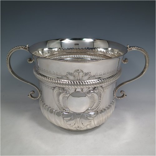 An Antique Victorian sterling silver large trophy cup, in the shape of a Porringer, having a round body with hand-chased fluted bands, a central vacant cartouche on one side, with two cast scroll side-handles, and sitting on a flat base. Made by Frazer & Haws of London in 1894. The dimensions of this fine hand-made antique silver trophy porringer cup are height 22 cms (8.75 inches), spread across handles 39 cms (15.25 inches), and it weighs approx. 1,512g (49 troy ounces).