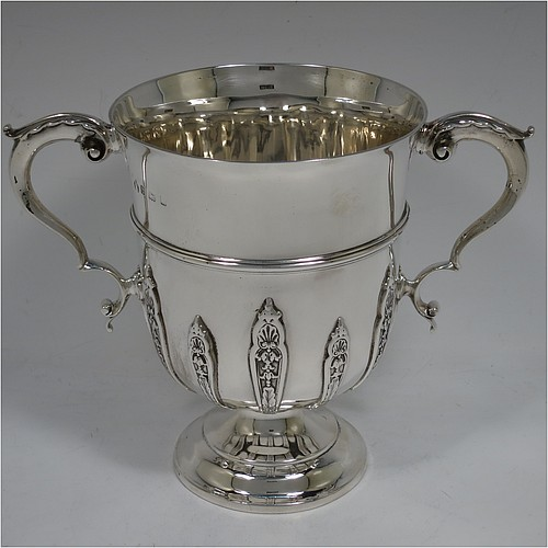 A very handsome Antique Edwardian Sterling Silver trophy cup, in a George II style, having a round body with applied floral strap-work decoration, two scroll side-handles with anthemion leaf thumb-pieces, a central applied girdle band, and all sitting on a stepped pedestal foot. Made by Elkington and Co., of Birmingham in 1908. The dimensions of this fine hand-made antique silver trophy cup are height 16 cms (6.3 inches), spread across arms 21 cms (8.25 inches), and it weighs approx. 510g (16.5 troy ounces).