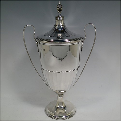 A very handsome Sterling Silver trophy cup and cover in a George III neoclassical style, having a round body with tapering sides and half-fluted decoration, with hand-chased reeded borders, two looped side-handles, an original cover with matching decoration and cast urn finial, and all sitting on a pedestal foot. Made by Robert Pringle  of London in 1923. The dimensions of this fine hand-made silver trophy cup and cover are height 33 cms (13 inches), spread across arms 21 cms (8.25 inches), and it weighs approx. 879g (28 troy ounces).