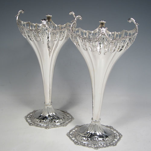 Sterling silver pair of very pretty table vases, having plain fluted bodies, with hand-pierced tops and applied cast floral and scroll borders, and sitting on matching hand-pierced pedestal feet. Made by Mappin and Webb of London in 1914. The dimensions of this fine hand-made silver pair of vases are height 27 cms (10.5 inches), width at top 13 cms (5 inches), and they weigh a total of 600g (19.3 troy ounces). Please note that these vases are not loaded.