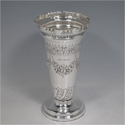 An Antique Victorian Sterling silver table flower vase, having a round body with tapering sides, with hand-chased floral and fluted decoration, and sitting on a pedestal foot. Made in Sheffield in 1897. The dimensions of this fine hand-made silver vase are height 16 cms (6.3 inches), and diameter at top 8.5 cms (3.3 inches).