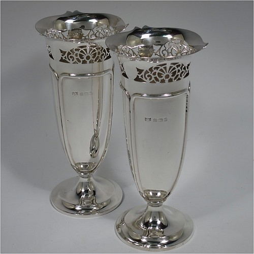 A Sterling Silver pair of table flower vases, having round bodies with tapering sides, with hand-chased fluted decoration, and hand-pierced floral style top borders, and sitting on pedestal feet. Made by Mappin and Webb of Birmingham in 1918. The dimensions of these fine hand-made silver pair of vases are height 17 cms (6.75 inches), diameter at top 7.5 cms (3 inches), and they weigh at total of approx. 384g (12.4 troy ounces). Please note that these vases are not loaded.