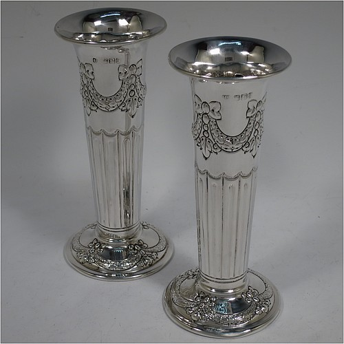 A very pretty Antique Victorian Sterling Silver pair of table flower vases, having round bodies with tapering sides and hand-chased neoclassical style decoration with half-fluting, ribbon bows, and swags, and sitting on pedestal feet. Made by Henry Atkins of Sheffield in 1892. The dimensions of these fine hand-made antique silver pair of vases are height 15 cms (6 inches), diameter at top 6.5 cms (2.5 inches), and they weigh at total of approx. 200g (6.5 troy ounces). Please note that these vases are not loaded.