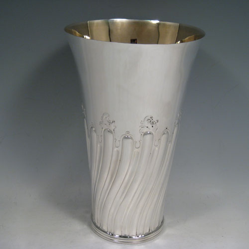 Antique Victorian sterling silver large table flower vase, having a tapering round body, with hand-chased swirl half-fluted decoration, an applied reeded band at the base, and a gold-gilt interior. Made by Susanah Brasted of London in 1889. The dimensions of this sterling silver vase are height 24 cms (9.5 inches), diameter at top 15 cms (6 inches). Weight approx. 612g (19.7 troy ounces).