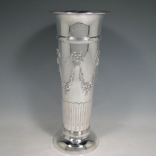 Antique Edwardian sterling silver large table flower vase, having a tapering round body, with hand-chased half-fluted decoration on the lower half, and hand-chased swags with bows on the upper half, applied reeded bands at the top and bottom, and sitting on a collet foot. Made by Goldsmiths and Silversmiths of London in 1906. The dimensions of this fine hand-made silver vase are height 30 cms (11.75 inches), diameter at top 12.5 cms (5 inches), and it weighs approx. 505g (16.3 troy ounces). Please note that this vase is not loaded.