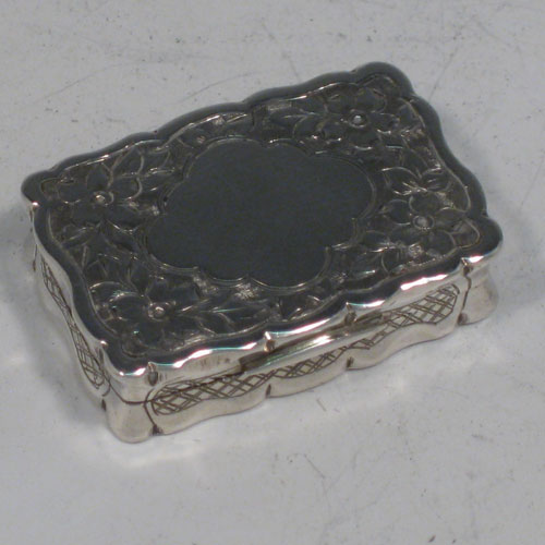 Antique Victorian sterling silver vinaigrette, having a rectangular shaped body with hand-engraved floral decoration (with roses and ferns), a hinged lid with vacant cartouche, and a gold-gilt interior with hinged hand-pierced and chased grill. Made by George Unite of Birmingham in 1838. The dimensions of this fine hand-made silver vinaigrette are length 3.5 cms (1.3 inches), and width 2.5 cms (1 inch).