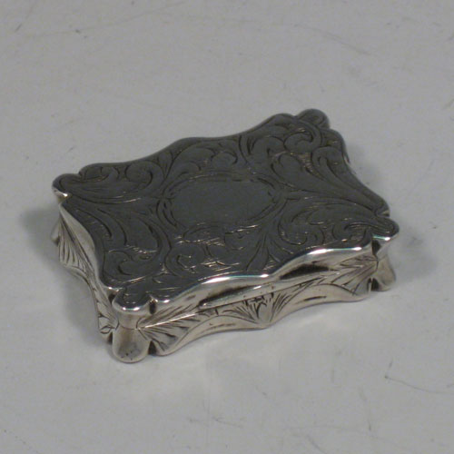 Antique Victorian sterling silver vinaigrette, having a rectangular shaped body with hand-engraved floral decoration and a vacant cartouche, a hinged lid, and a gold-gilt interior with hinged hand-pierced and chased grill. Made by Edward Smith of Birmingham in 1843. The dimensions of this fine hand-made silver vinaigrette are length 3.5 cms (1.3 inches), and width 2.5 cms (1 inch).