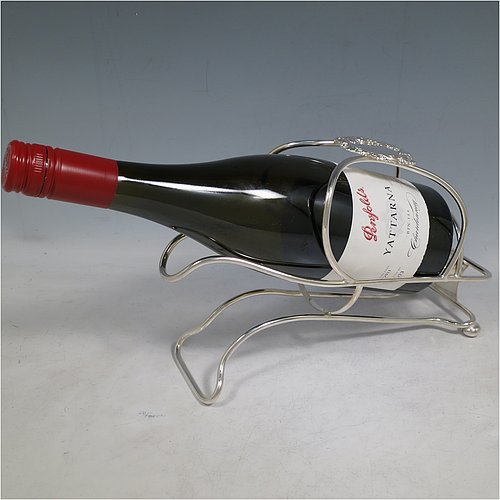 An Antique Victorian Silver Plated wine bottle cradle or holder, having a wire-work body with a cast wine-label style cartouche attached to the handle, and sitting on a base with two cushion feet. Made in Sheffield in ca. 1880. The dimensions of this fine hand-made antique silver wine bottle holder or cradle are length 24 cms (9.5 inches), width 10 cms (4 inches), and height 16.5 cms (6.5 inches). Please note that this wine bottle cradle will accept a standard 75cl, (bottle shown for display purposes only).