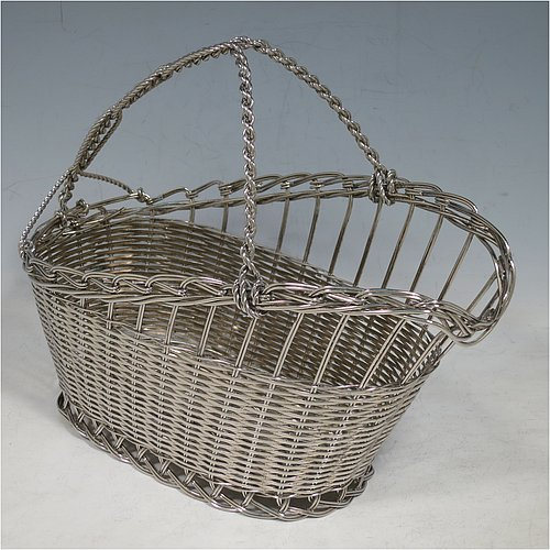An Antique Victorian Silver Plated wine bottle cradle or holder, having an oval straight-sided body with tapering sides, with an attached carrying handle, and sitting on a flat base, all made in a basket-weave style with individual wire-work decoration. Made in Sheffield in ca. 1900. The dimensions of this fine hand-made antique silver wine bottle holder or cradle are length 23 cms (9 inches), width 12 cms (4.75 inches), and height 18 cms (7 inches). Please note that this wine bottle cradle will accept a standard 75cl, (bottle shown for display purposes only).