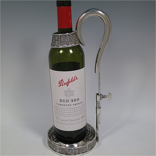 An Antique Victorian Silver Plated wine bottle cradle or holder, having a round straight-sided base with basket-weave hand-pierced decoration, a plain sliding scroll handle with matching basket weave neck and retaining screw. Made by J. and B. of Sheffield in ca. 1870. The dimensions of this fine hand-made antique silver-plated wine bottle holder or cradle are height 26 cms (10 inches), or 33 cms (13 inches) extended, and diameter of base 11.5 cms (4.5 inches). Please note that this wine bottle cradle or holder will accept a 75cl bottle, (bottle shown for display purposes only).