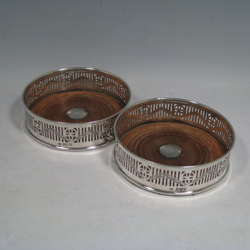 Sterling silver pair of wine bottle table coasters, having round bodies with hand-pierced decoration and engraved swags, with wood-turned bases and silver buttons, and applied beaded borders. Made by Henry Freeman Ltd., of London in 1913. The dimensions of these wine coasters are diameter 13 cms (5 inches), height 4 cms (1.5 inches).