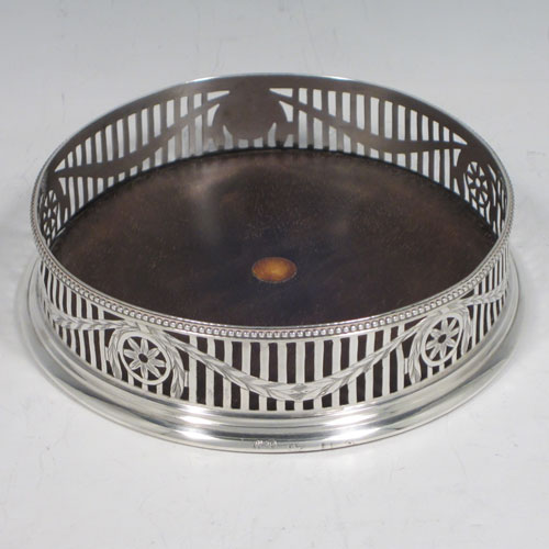 Antique Georgian Neoclassical sterling silver large wine table coaster, having a round hand-pierced body, with swags of laurel leaves and an applied bead border, and a wood-turned base with ivory button. Made by William Plummer of London in 1776. The dimensions of this fine hand-made silver wine coaster are diameter 13 cms (5 inches), and height 3 cms (1.25 inches).