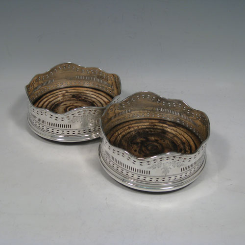 Antique Georgian Old Sheffield plated pair of table wine bottle coasters, having wavey bead-edged borders, hand-pierced and engraved bodies, and original oak wood-turned bases. Made in ca. 1790. Diameter 13 cms (5 inches), height 6 cms (2.25 inches). Please note that the wooden bases are stained.