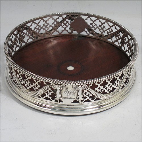 An Antique Georgian Neoclassical style Sterling Silver wine bottle table coaster, having a round hand-pierced body, with applied ribbons and swags on a hand-pierced body, together with an applied rope-twist or gadroon border, and a wood-turned base with bone button. Made by Elizabeth Jones of London in 1774. The dimensions of this fine hand-made antique silver wine bottle coaster are diameter 11 cms (4.3 inches), and height 3.5 cms (1.3 inches).