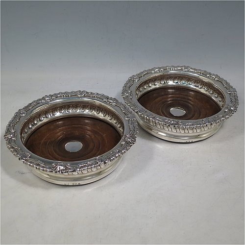An Antique Georgian Sterling Silver pair of table wine bottle coasters, in a Regency style having round bodies with a band of hand-chased fluted decoration, applied gadroon, scroll, & shell borders, and wood turned bases with silver buttons. Made S. C. Younge & Co of Sheffield in 1815. The dimensions of this fine pair of hand-made antique silver wine bottle coasters are diameter 16 cms (6.3 inches), and height 4 cms (1.5 inches).