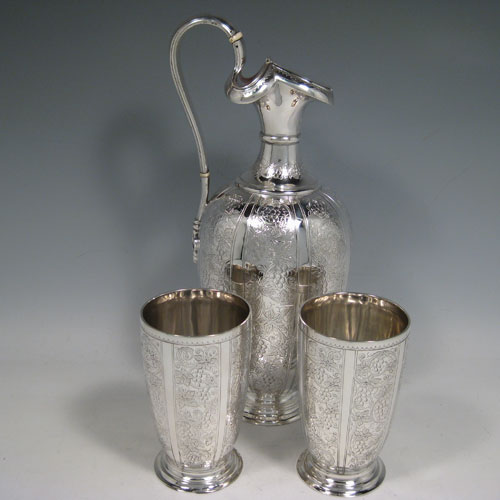 Antique Victorian sterling silver wine ewer and two beakers, having hand-engraved grape-vine and leaf decoration. Made by Martin Hall and Co., of London in 1878. Height of ewer 28 cms (11 inches), height of beakers 11.5 cms (4.5 inches). Total weight approx. 805g (26 troy ounces).
