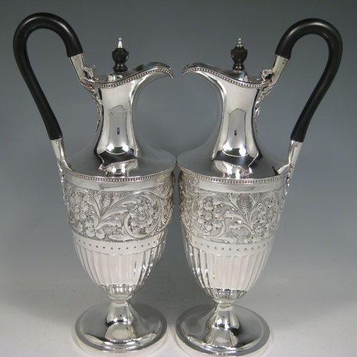 Antique Victorian sterling silver pair of Neoclassical style wine ewers, having round bodies with tapering sides, all hand-chased with floral bands and half-fluting, wooden scroll handles, hinged lids with wooden finials, applied bead-edged borders, and all sitting on pedestal feet. Made by William Hutton of London in 1896 and 1899. The dimensions of these fine hand-made silver wine ewers are height 32 cms (12.5 inches), length 15 cms (6 inches), and they weigh a total of 1,085g (35 troy ounces). Please note that because these ewers were made within three years of each other the body of the 1896 ewer is slightly larger in diameter.